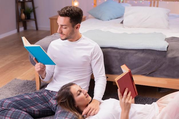 Jovem casal lendo livros no chão