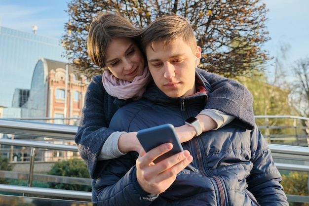 Jovem casal lendo o texto no telefone, fundo de cidade de primavera
