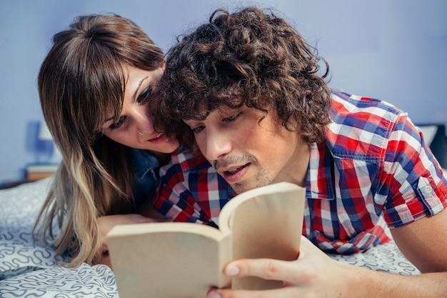 Jovem casal lendo um livro juntos, deitado na cama Foto Premium