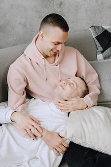 Jovem casal lgbtq romântico, passando o dia acariciando e relaxando no sofá. conceito de estilo de vida familiar diferente.
