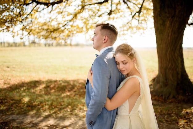 Jovem casal lindo abraçando em seus vestidos de noiva no parque outono.