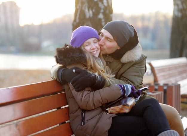 Jovem casal lindo abraçando no banco no parque