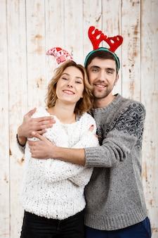 Jovem casal lindo abraçando sorrindo por cima da parede de madeira