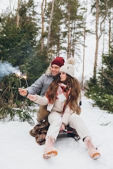 Jovem casal lindo abraços e queima estrelinhas em uma floresta de coníferas de inverno enquanto está sentado em um trenó. um parque com árvores de natal ao fundo. espírito de natal. tingimento.