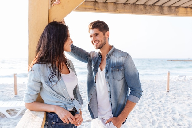 Jovem casal lindo alegre flertando na praia
