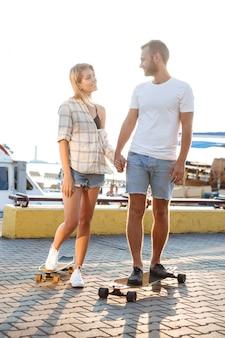 Jovem casal lindo andando na beira-mar, sorrindo, andar de skate.