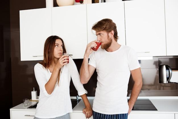 Jovem casal lindo bebendo suco em pé na cozinha.