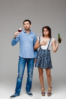 Jovem casal lindo bebendo vinho e cerveja sobre parede cinza