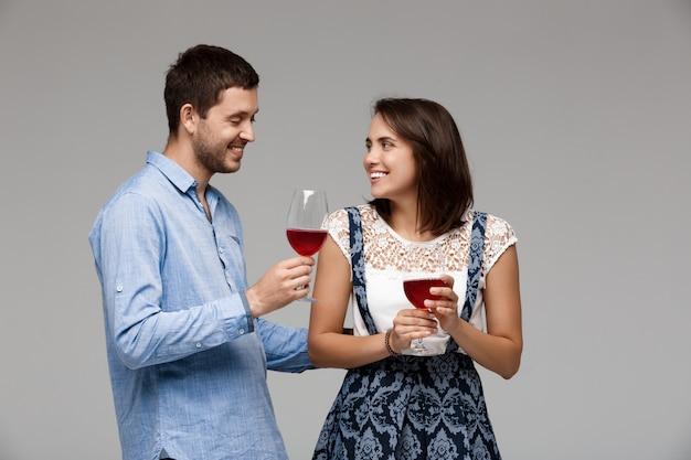 Jovem casal lindo bebendo vinho, sorrindo sobre parede cinza