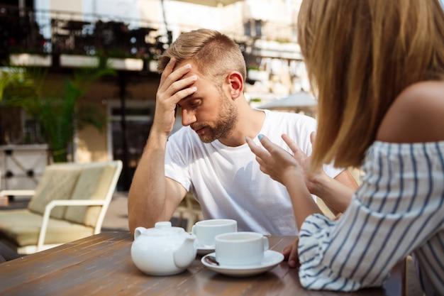 Jovem casal lindo brigando, sentado no café.