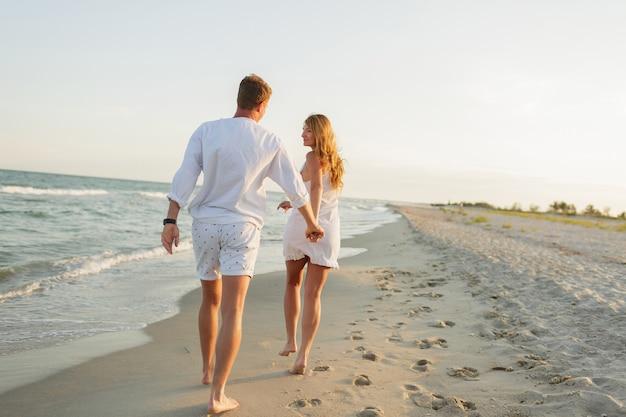 Jovem casal lindo caminha à beira-mar ao pôr do sol.