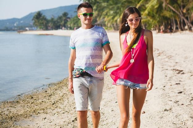 Jovem casal lindo caminhando em uma praia tropical na tailândia, de mãos dadas, sorrindo, feliz, se divertindo, óculos de sol, roupa hipster, estilo casual, lua de mel, férias, verão, ensolarado
