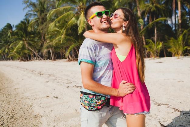 Jovem casal lindo caminhando em uma praia tropical, tailândia, abraçando, rindo, óculos de sol, se divertindo, roupa hipster, estilo casual, lua de mel, férias, verão, ensolarado, clima romântico