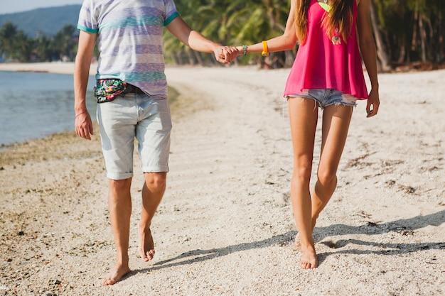 Jovem casal lindo caminhando em uma praia tropical, tailândia, de mãos dadas, vista de trás, roupa hipster, estilo casual, lua de mel, férias, verão, clima romântico, close-up de pernas, detalhes