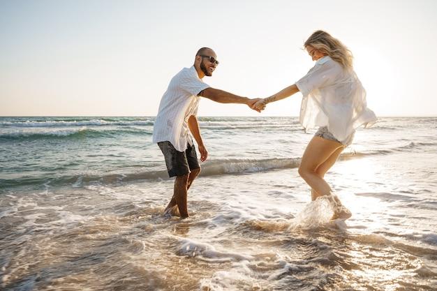 Jovem casal lindo caminhando na praia perto do mar