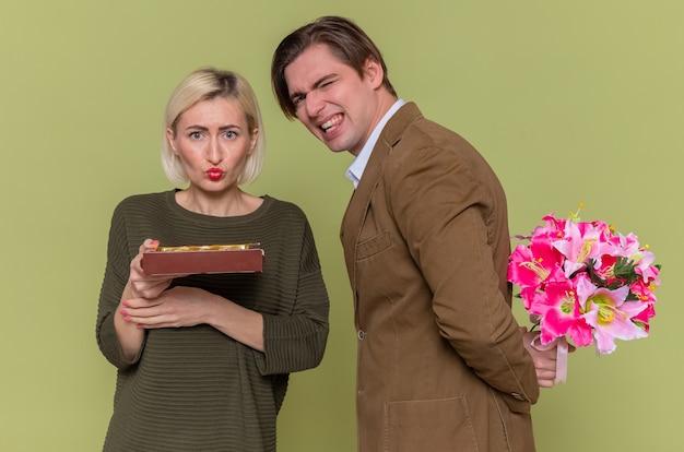 Jovem casal lindo com caixa de bombons de chocolate comemorando o dia dos namorados