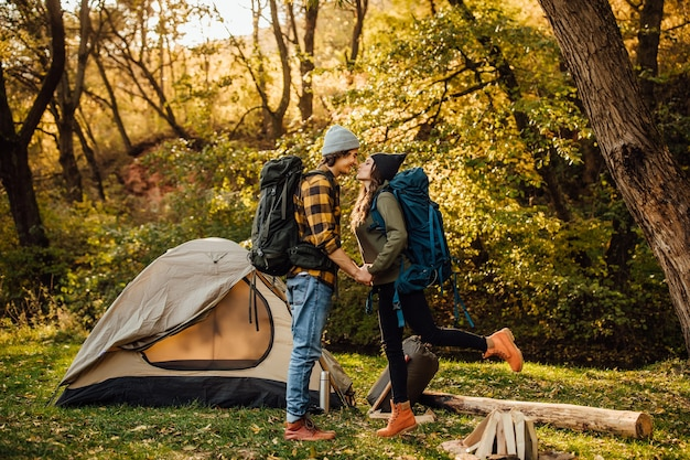 Jovem casal lindo com mochila de caminhada se beijando na floresta perto da barraca