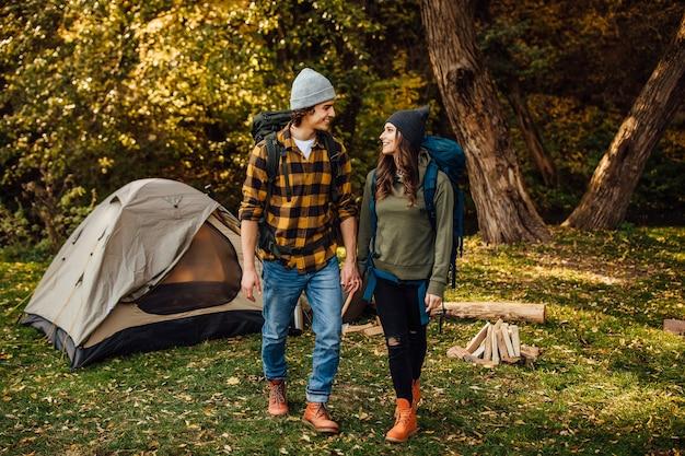 Jovem casal lindo com mochilas de caminhada vai acampar
