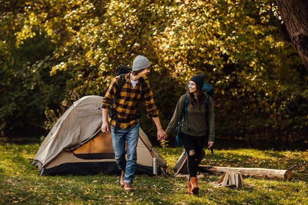 Jovem casal lindo com mochilas de caminhada vai fazer trekking
