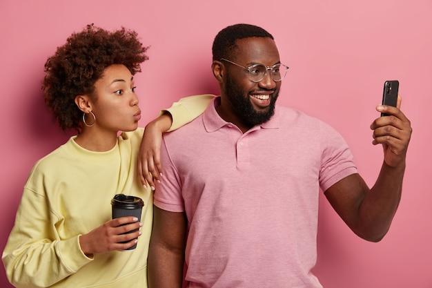 Jovem casal lindo com pele escura tira foto de si mesmo, posa para a câmera do smartphone moderno, sorri e dobra os lábios, faz selfie durante o tempo de lazer