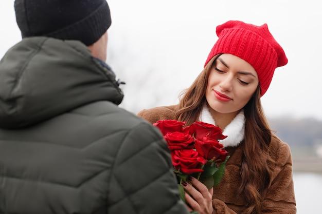 Jovem casal lindo com rosas vermelhas ao ar livre