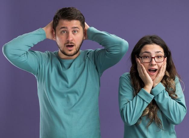Jovem casal lindo com roupas azuis casuais espantado e surpreso com o homem e a mulher em pé sobre a parede roxa