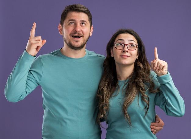 Jovem casal lindo com roupas casuais azuis, homem e mulher olhando para cima com um sorriso nos rostos inteligentes, mostrando os dedos indicadores em pé sobre a parede roxa