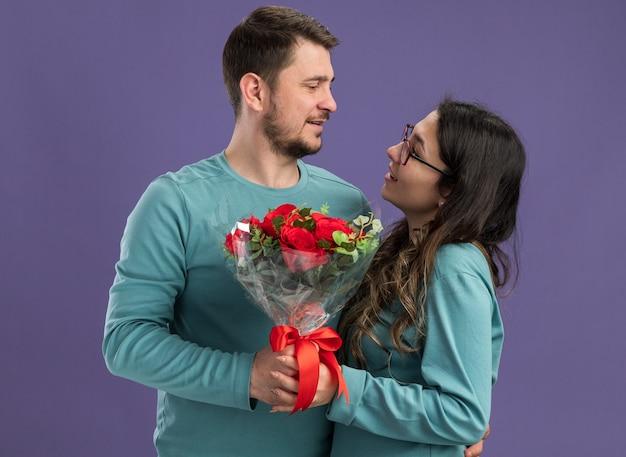 Jovem casal lindo com roupas casuais azuis, homem e mulher segurando um buquê de rosas, olhando um para o outro, felizes e apaixonados, em pé sobre a parede roxa