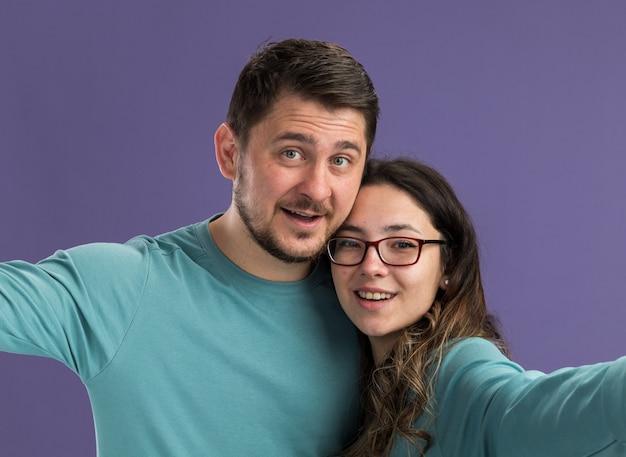 Jovem casal lindo com roupas casuais azuis, homem e mulher, sorrindo alegremente, felizes e apaixonados juntos em pé sobre a parede roxa