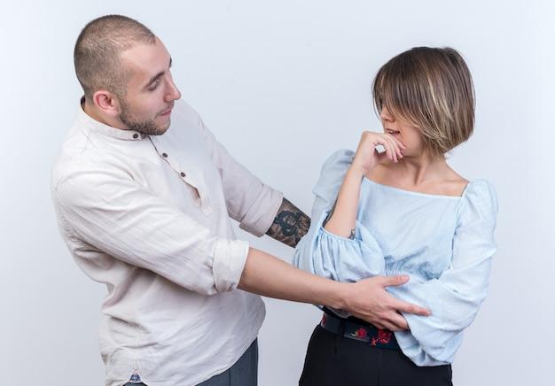 Jovem casal lindo com roupas casuais, homem e mulher brigando, olhando um para o outro em pé sobre uma parede branca
