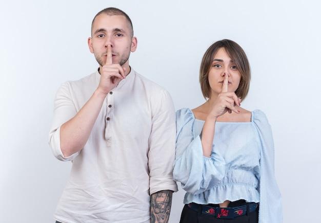 Jovem casal lindo com roupas casuais, homem e mulher fazendo gesto de silêncio com os dedos nos lábios, em pé sobre uma parede branca