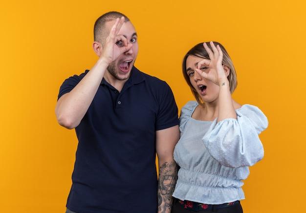 Jovem casal lindo com roupas casuais homem e mulher feliz e alegre fazendo sinal de ok olhando por entre os dedos em pé