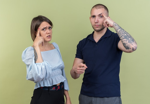 Jovem casal lindo com roupas casuais, homem e mulher parecendo confuso, apontando com o dedo indicador para as têmporas em pé