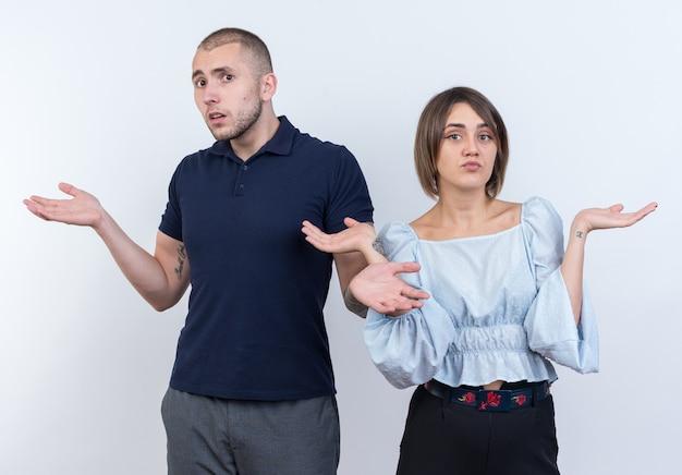 Jovem casal lindo com roupas casuais, homem e mulher, parecendo confusos, abrindo os braços para os lados em pé