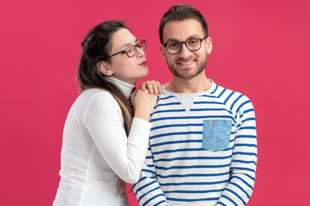Jovem casal lindo com roupas casuais, mulher feliz vai beijar seu namorado sorridente, comemorando o dia dos namorados em pé sobre a parede rosa