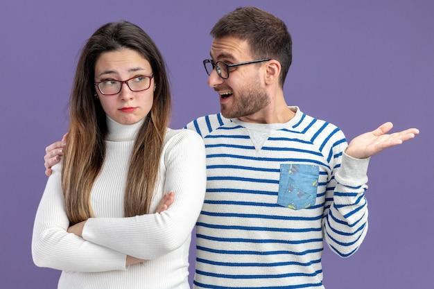 Jovem casal lindo com roupas casuais, sorrindo, olhando para a namorada triste, conceito do dia dos namorados em pé sobre a parede roxa