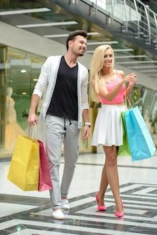 Jovem casal lindo com sacos para fazer compras.