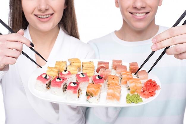 Jovem casal lindo com um prato de sushi.