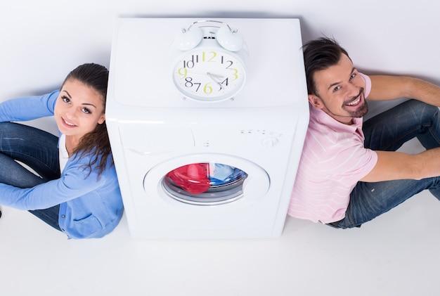 Jovem casal lindo com uma máquina de lavar.