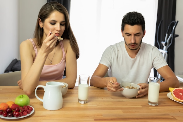 Jovem casal lindo come cereal de café da manhã com frutas e leite.