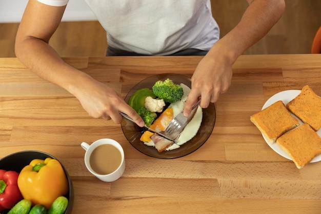 Jovem casal lindo comer alimentos orgânicos saudáveis no café da manhã.