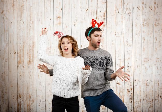 Jovem casal lindo dançando se divertir ao longo da parede de madeira