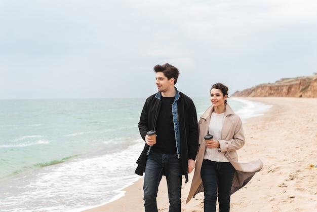 Jovem casal lindo de casacos caminhando na praia, tomando café para viagem