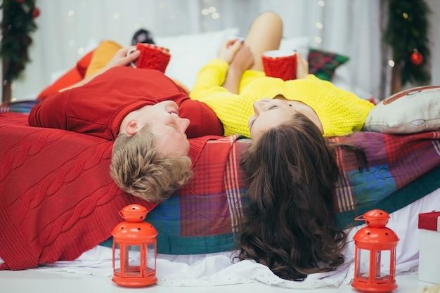 Jovem casal lindo deitado na cama e se abraçando em uma decoração de natal