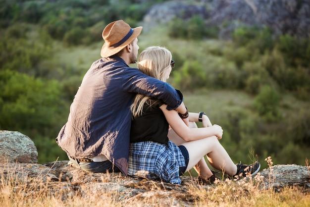 Jovem casal lindo descansando, apreciando a vista no canyon