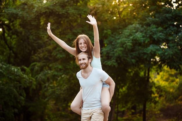 Jovem casal lindo descansando, caminhando no parque, sorrindo, alegrando-se ao ar livre