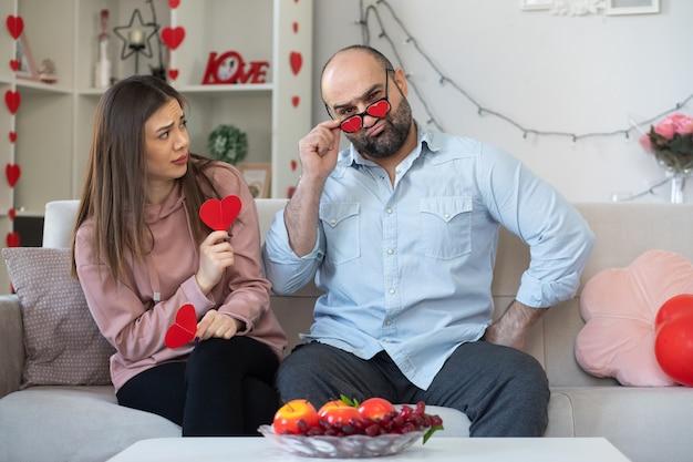 Jovem casal lindo descontente homem com óculos engraçados e mulher confusa com corações feitos de papelão, celebrando o dia internacional da mulher, sentado em um sofá em uma sala iluminada
