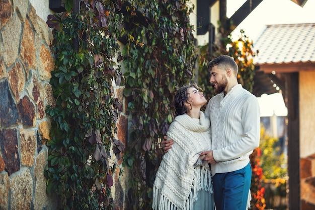 Jovem casal lindo e feliz, homem e mulher em um lindo jardim no quintal de uma casa de campo