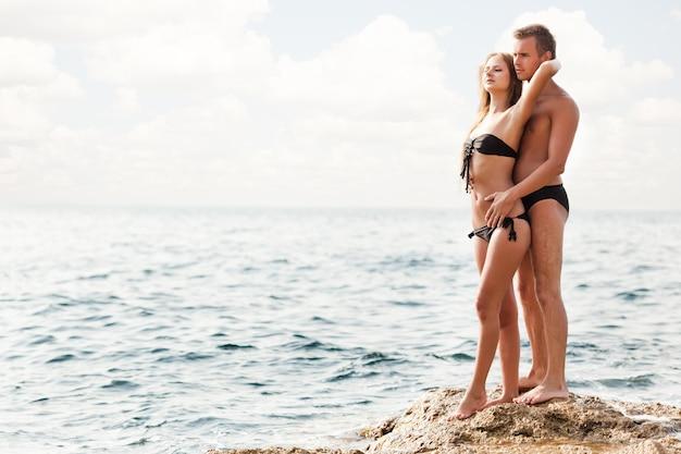 Jovem casal lindo e feliz mulher e homem em pé sobre as rochas