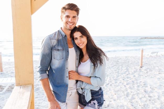 Jovem casal lindo e sorridente olhando um para o outro em pé na praia